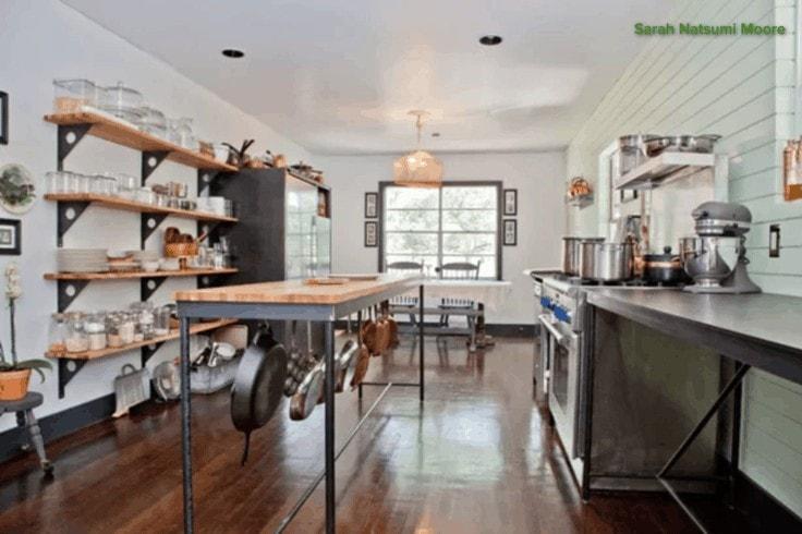 Organized kitchen with pot rack under island counter.
