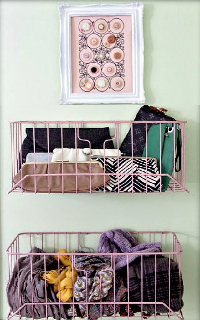Beauty accessories stored in pink wire baskets hanging on the wall.