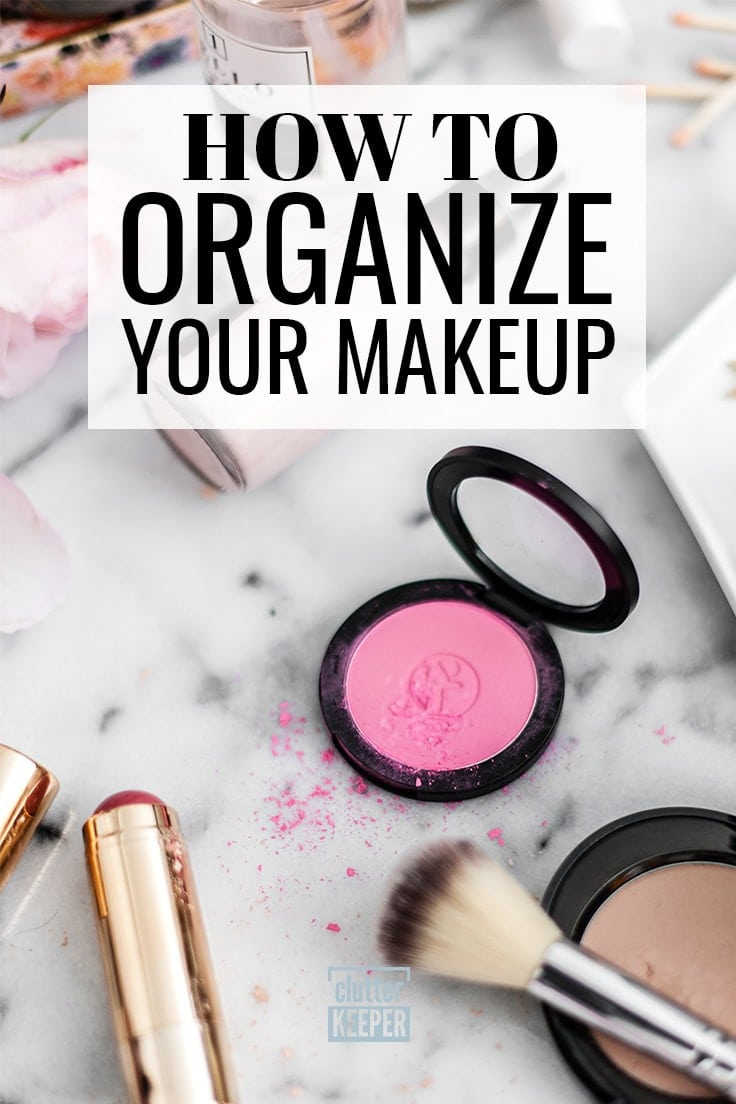 How to organize your makeup - Makeup on top of a marble bathroom countertop including two tubes of lipstick, blush compact and brush and foundation powder