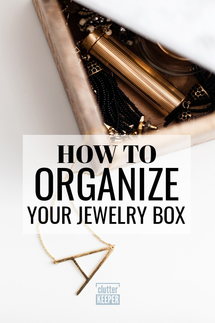 How to organize your jewelry box - Open jewelry box with a necklace hanging out of the side. The necklace has a pendant in the shape of a letter A.