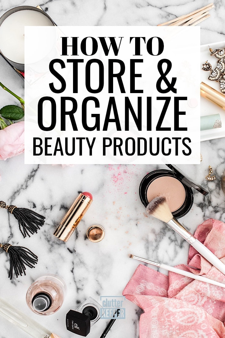 How to store and organize beauty products - Marble bathroom countertop covered with open makeup containers including a tube of lipstick, blush compact and brush, nail polish, a candle, two pink flowers and several pairs of earrings