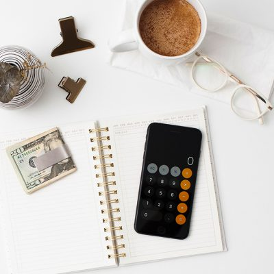 A calendar sitting open on a desk with a calculator and a money clip with a $20 bill sitting on top of it to help you plan a garage sale. Next to it is a cup of coffee, a pair of glasses and two binder clips.