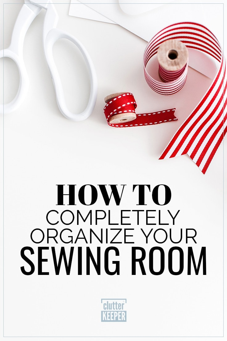 Title on Image: How to Completely Organize Your Sewing Room. Image shows a spool of red ribbon, a pair of scissors with a white handle and a spool of wide white and red striped ribbon for craft and sewing projects.