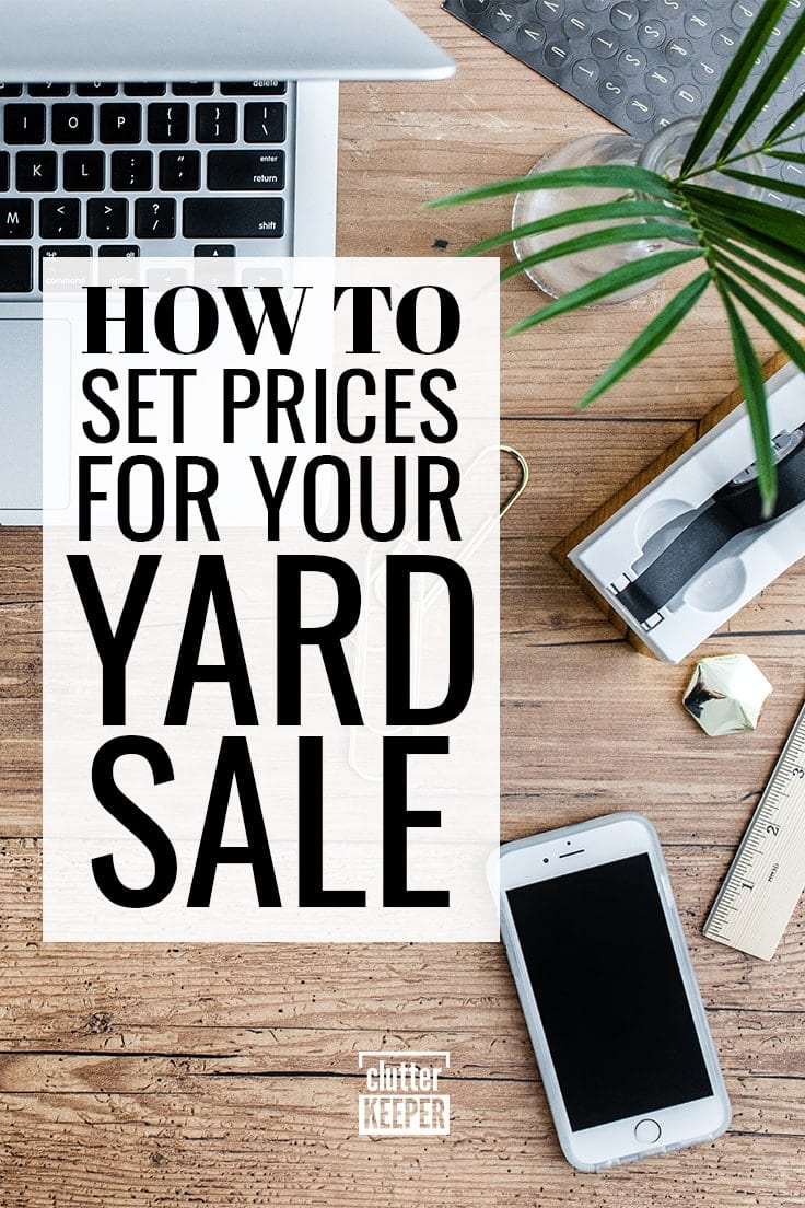 How to set prices for your yard sale. An overhead shot of an open laptop computer and a cell phone being used to calculate pricing for a garage sale. Nearby are a wooden ruler, a tape dispenser and a vase with cut ferns.