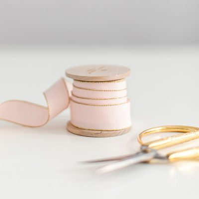The image shows a spool or ribbon and a pair of scissors with gold handles to illustrate your complete guide to sewing room organization.