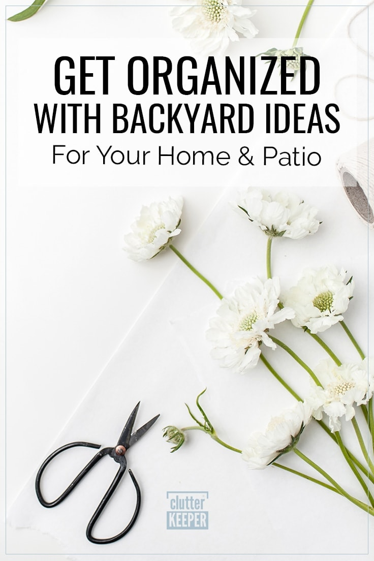 Get Organized with Backyard Ideas for Your Home and Patio; Overhead shot of an open pair of metal gardening sheers with white fresh flowers that were recently cut from the backyard.