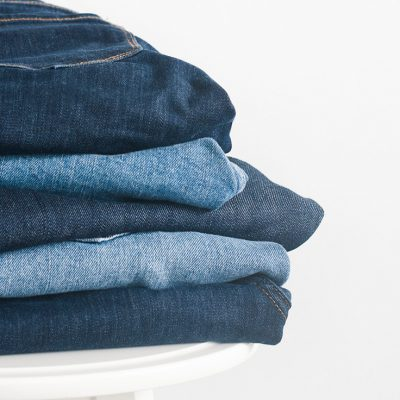 5 pairs of kids' sized jeans folded neatly in a stack on top of a white stool. The neat pile demonstrates the importance of organizing kids clothes.