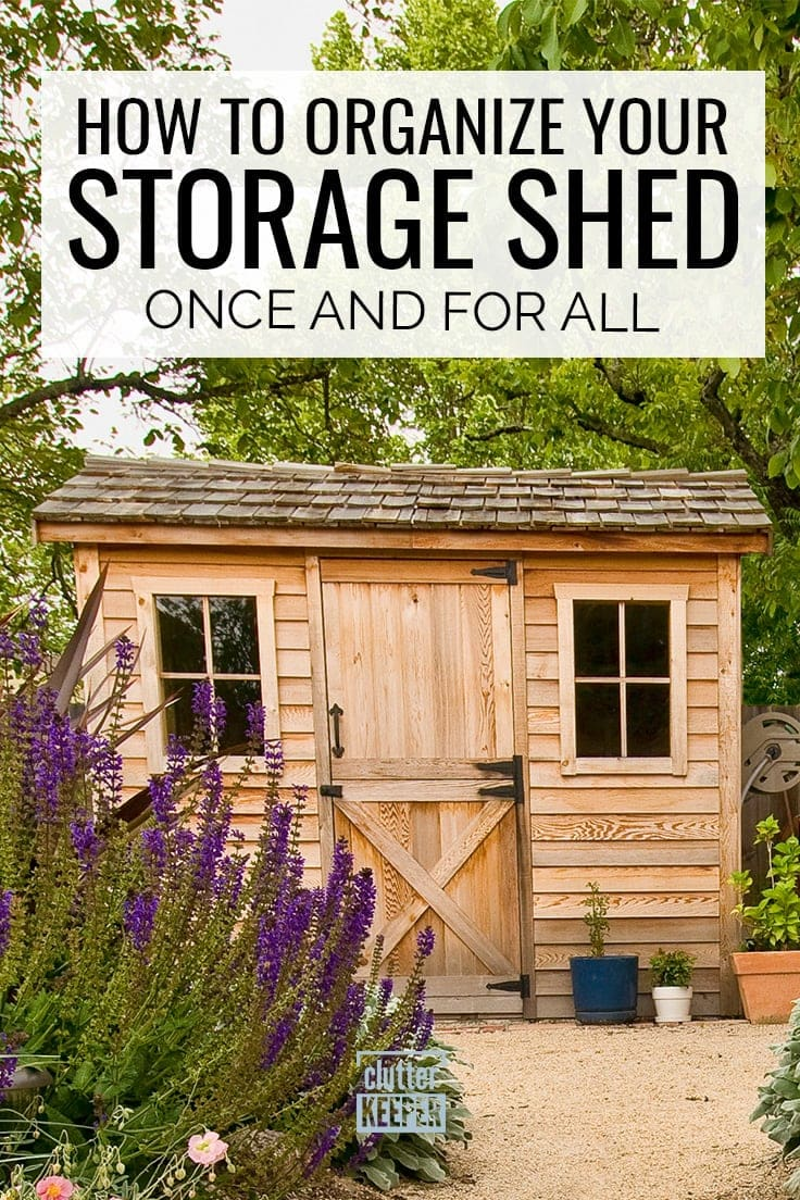 How to Organize Your Storage Shed Once and for All - front of a storage shed with wood siding and a rustic barn door. Lush purple flowers.