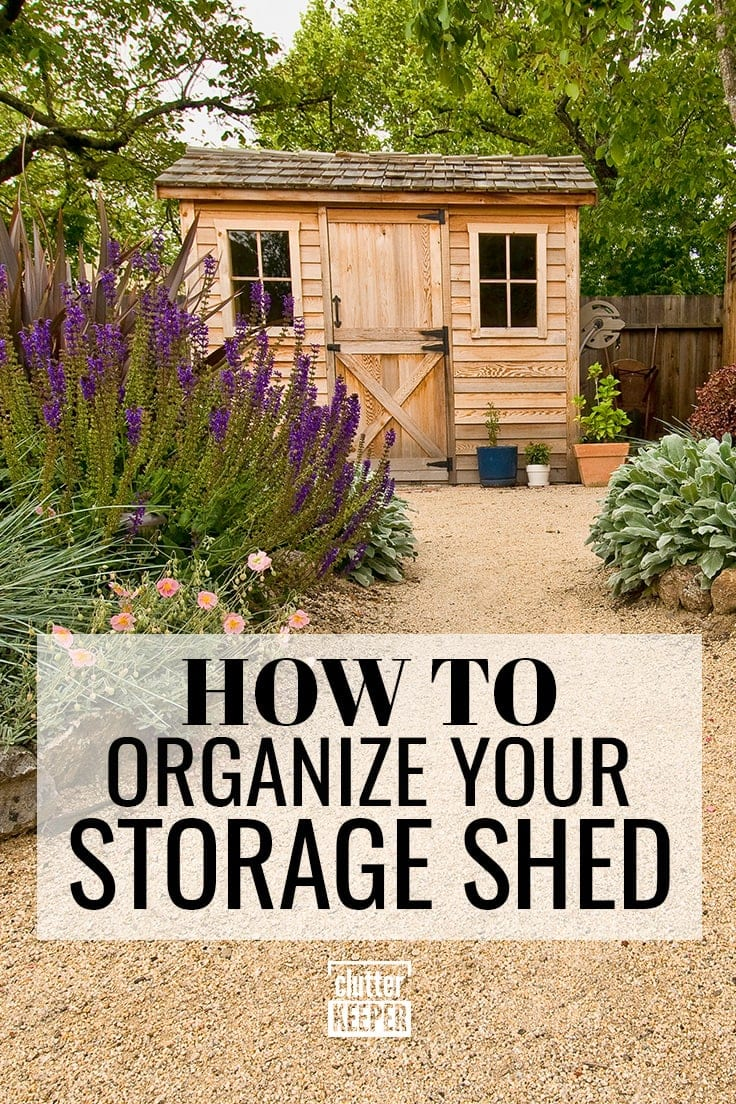 How to Organize Your Storage Shed. Front of a storage shed with wood siding and a rustic barn door. Lush purple flowers.