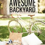 Ideas to Plan an Awesome Backyard; a blanket on the grass in the backyard with a picnic basket on top along with two pillows, a pair of sunglasses, magazines, a camera and a bunch of fresh cut pink flowers wrapped in paper. Behind the picnic is a bicycle on the grass and a large tree.