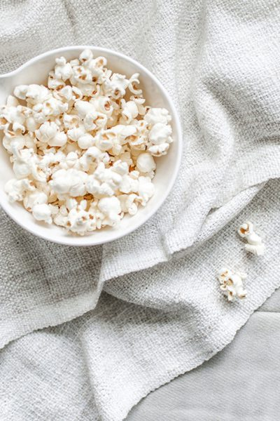 A full bowl of popcorn on a blanket on a couch with three loose kernels of popcorn near by, ready for family movie night after you organize your movies and video games.