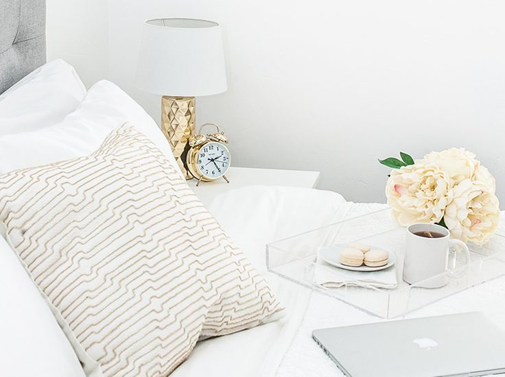 A bed from the side with pillows and a fluffy comforter. On top of the bed is a Mac laptop and a tray with macarons, a cup of coffee and flowers. Next to the bed is an old fashioned alarm clock and a small lamp on a bed side table.