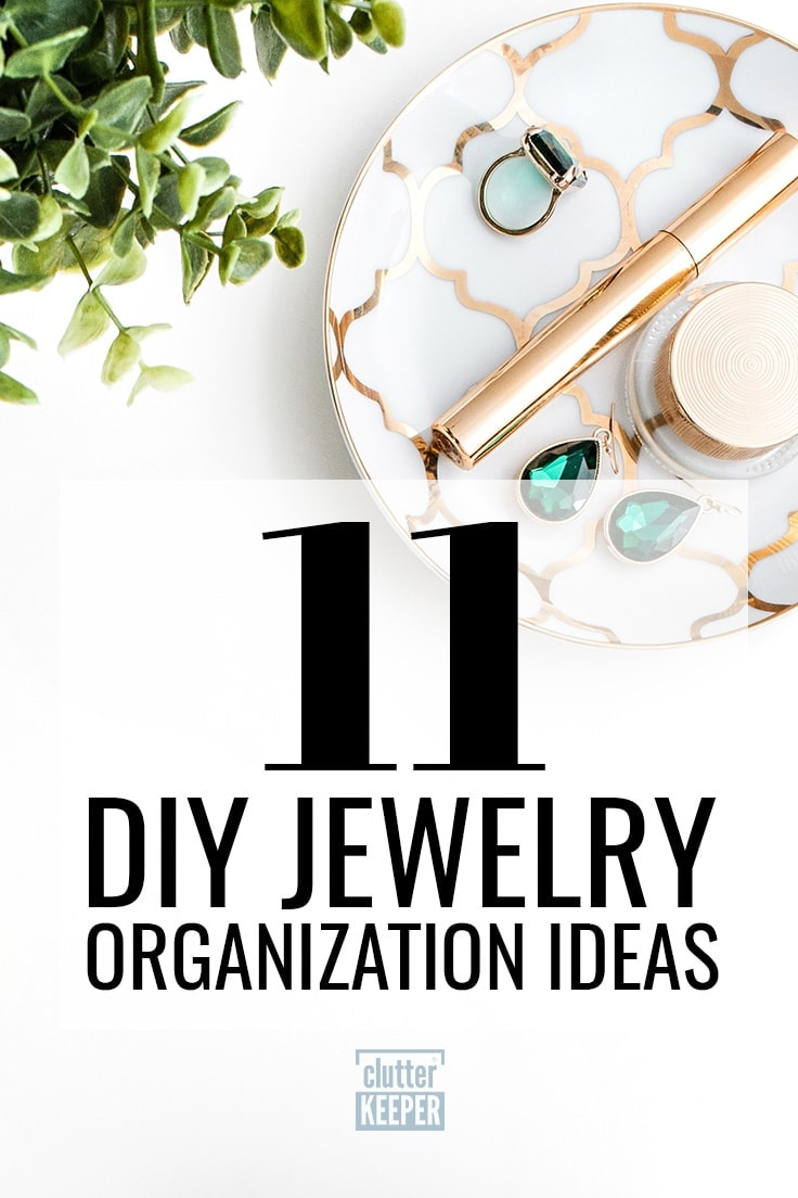 11 DIY jewelry organization ideas, an overhead view of a green plant and a small gold and white plate filled with make-up, earrings and a large emerald ring