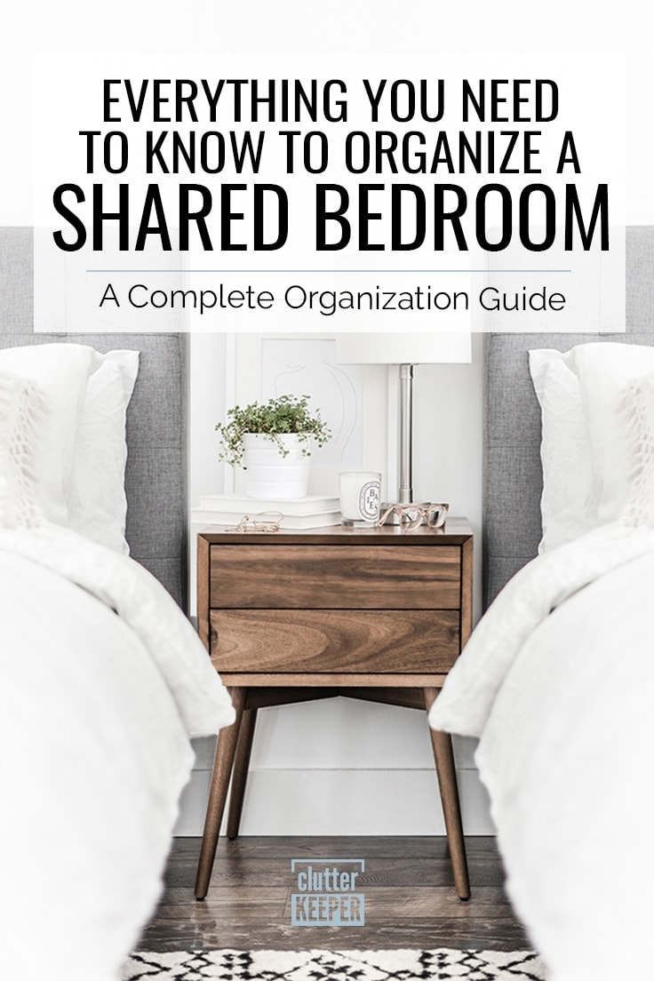 Everything You Need to Know to Organize a Shared Bedroom: A Complete Organization Guide, two beds with fluffy comforters and upholstered headboards next to a wood nightstand. On the nightstand there is a lamp, books, candle and glasses