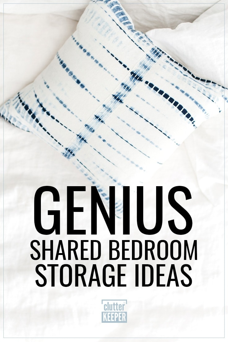 Genius Shared Bedroom Storage Ideas, a rumpled white comforter on an unmade bed along with a blue and white tie-dyed throw pillow.