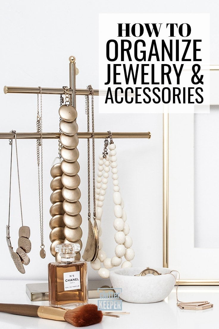 How to organize jewelry and accessories. A close-up of the top of a dresser, focused on a tall necklace holder shaped like a T with two cross bars. Large metal gold necklaces are hanging from the jewelry organizer. A white bowl below the necklace holder contains a watch and a necklace.