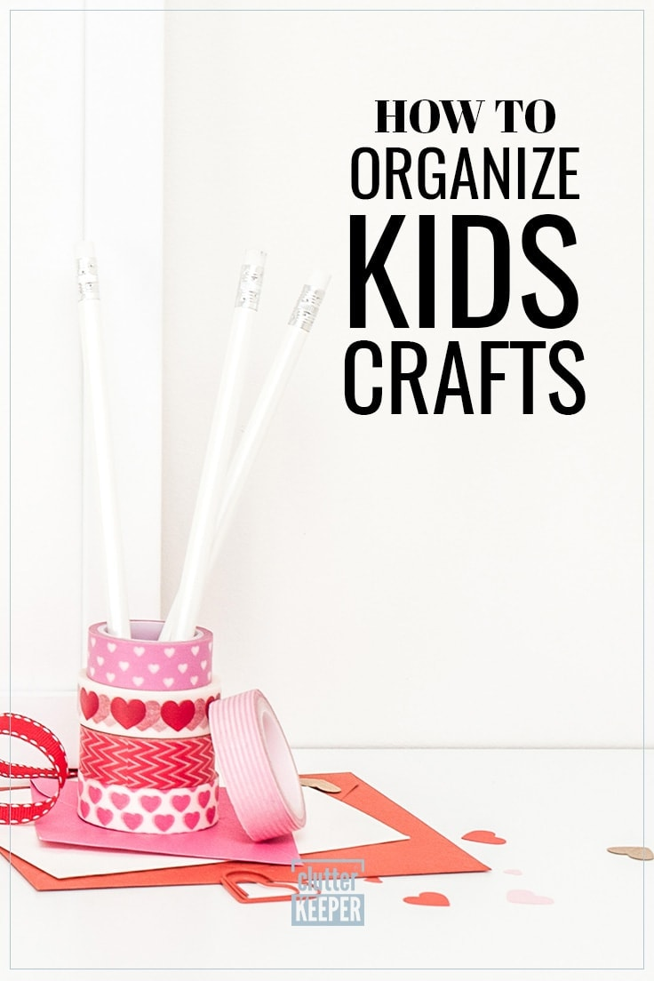 How to Organize Kids Crafts, rolls of red and pink patterned washi tape and ribbon stacked on top of one another as a pencil holder. Papers are scattered for children's crafts.