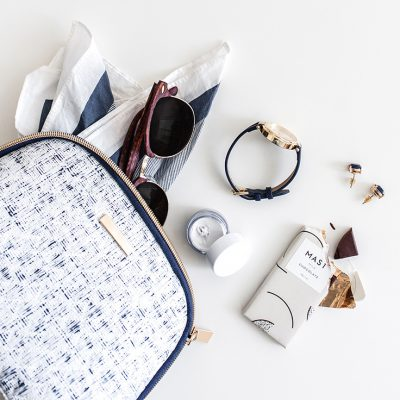 Blue and white small tweed bag on its side with accessories and contents spilling out, including a scarf, sunglasses, wrist watch, earrings and a partially eaten chocolate bar.