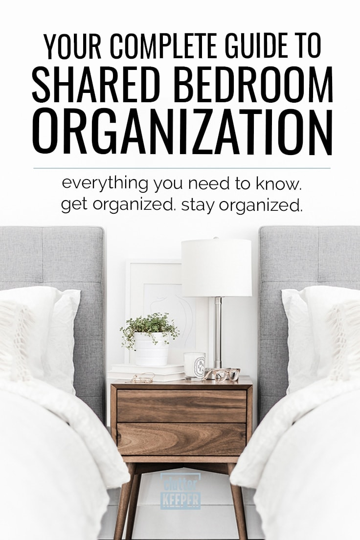 Your Complete Guide to Shared Bedroom Organization. Everything you need to know. Get Organized. Stay organized. Two beds with fluffy comforters and upholstered headboards in a shared bedroom next to a wood nightstand. On the nightstand there is a lamp, books, candle and glasses