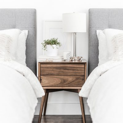two beds with fluffy comforters and upholstered headboards in a shared bedroom next to a wood nightstand. On the nightstand there is a lamp, books, candle and glasses