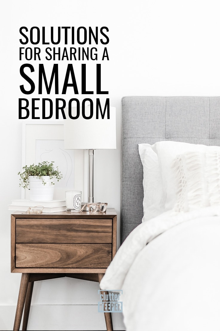 Solutions for Sharing a Small Bedroom, a bed with a fluffy comforter and upholstered headboard next to a wood nightstand. On the nightstand there is a lamp, books, candle and glasses