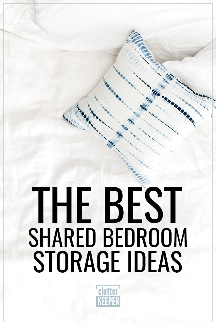 The Best Shared Bedroom Storage Ideas, a rumpled white comforter on an unmade bed along with a blue and white tie-dyed throw pillow.