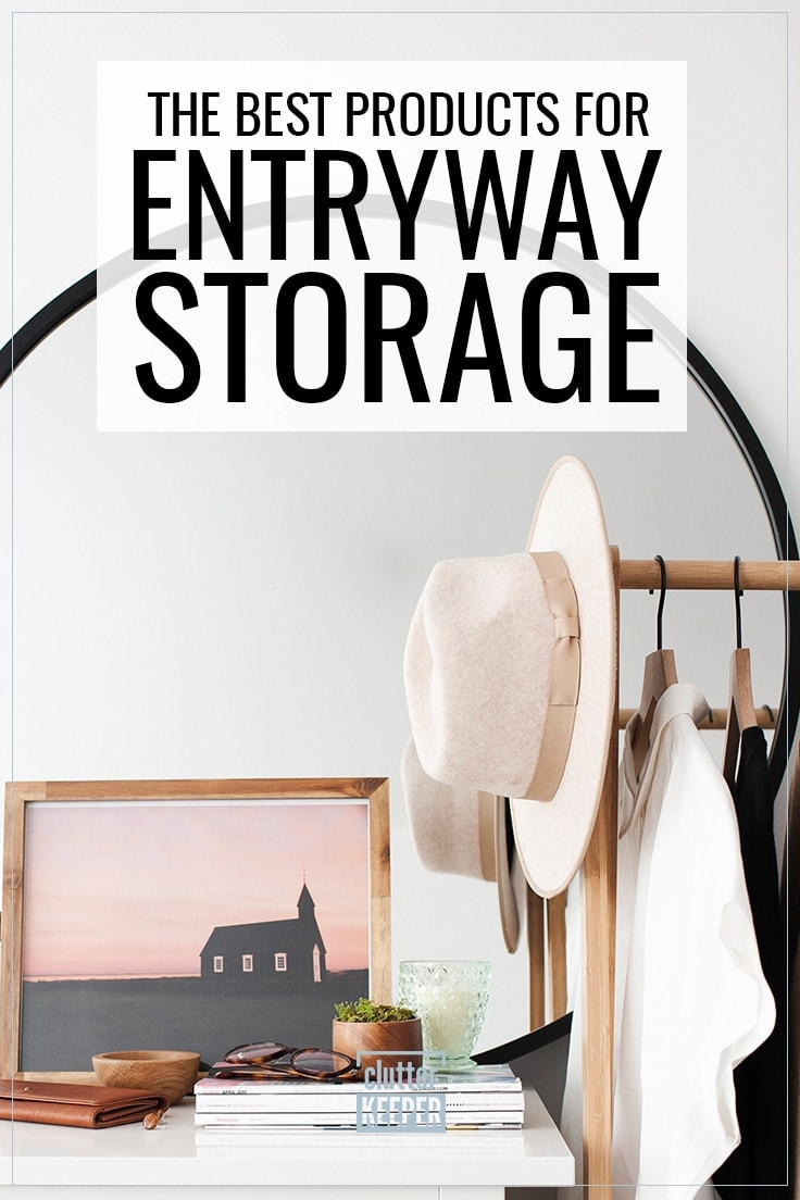 The Best Products for Entryway Storage, an entry way table covered with home decor including a large photo of a house, a stack of magazines, candle, eyeglasses, a wooden bowl and a leather purse. Coats and a hat hanging on hangers.