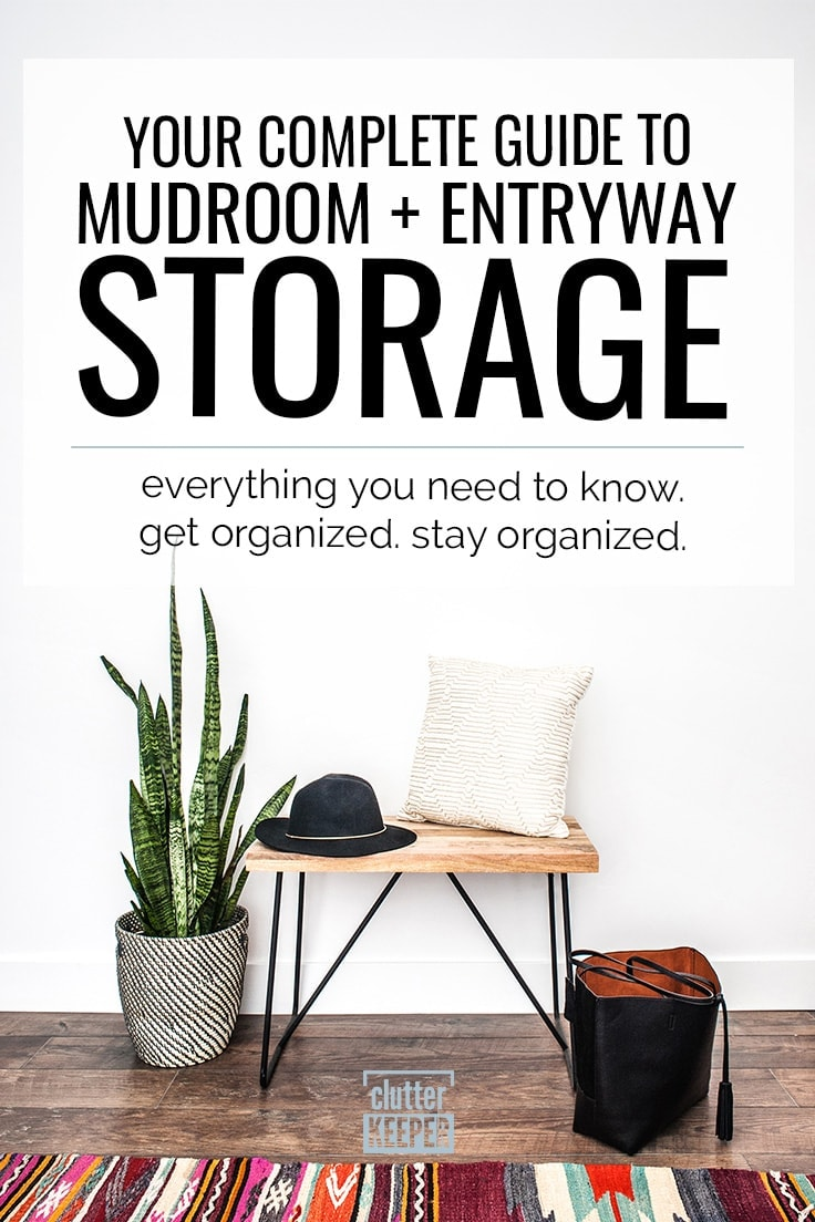 Your Complete Guide to Mudroom and Entryway Storage: Everything You Need to Know. Get Organized. Stay Organized. An entryway table in a mudroom topped with a black hat and a fluffy pillow next to a large plant, an open purse and a large patterned rug.