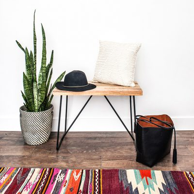 An entryway table in a mudroom topped with a black hat and a fluffy pillow next to a large plant, an open purse and a large patterned rug.