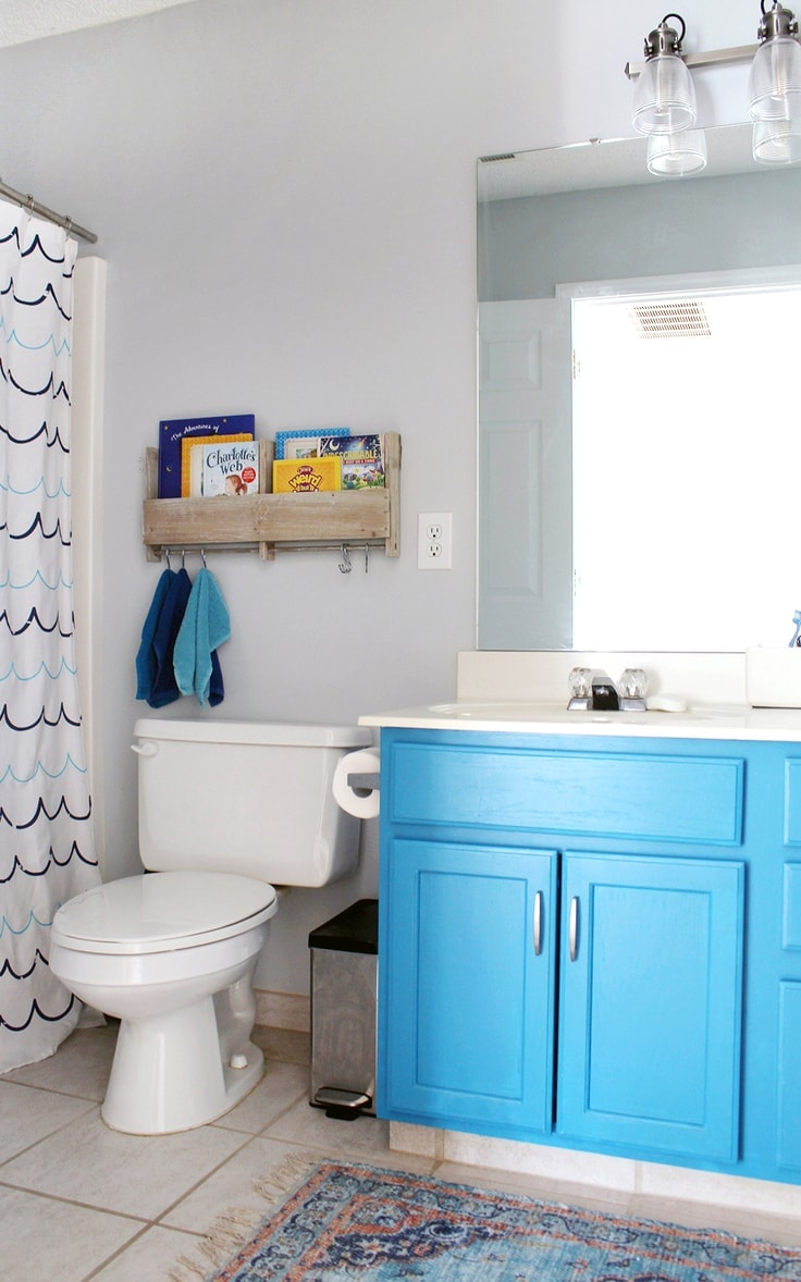 Hanging up washcloths and books on the wall in a bathroom to save space.