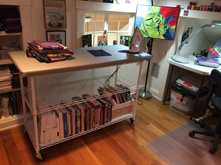 A rolling ironing cart with storage for a craft room.