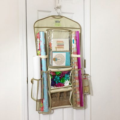 Clutter Keeper® Hanging Gift Wrap Organizer filled with birthday cards, gift wrap and gift bags on a closet door.