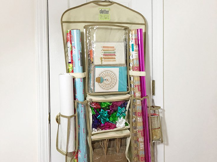 Clutter Keeper Hanging Gift Wrap Organizer filled with birthday cards, gift wrap and gift bags on a closet door.