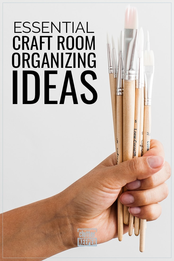 Essential Craft Room Organizing Ideas, a hand holding a bunch of paint brushes