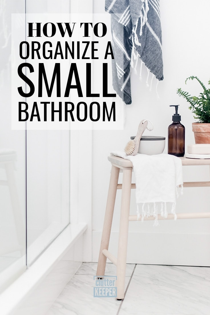 How to Organize a Small Bathroom, a small wooden stool next to the shower in a bathroom with tile floors. On top of the stool is a plant, a bar of soap, a glass bottle with pump, a towel and a scrub brush. Another towel is hanging on the wall by the shower.