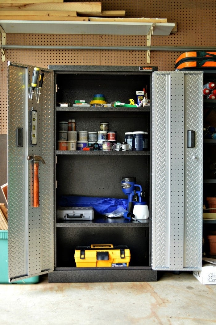 A metal storage shed inside a garage.