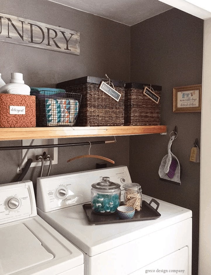 Baskets on a shelf and a breakfast tray on top of a washing machine holding laundry supplies