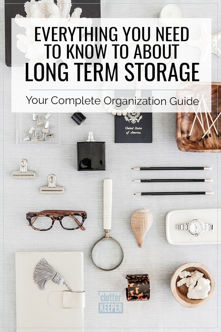 Everything you need to know about long term storage, your complete organization guide, overhead image of reading glasses, a white leather journal or diary with a tassel, a bracelet, a magnifying glass, a souvenir shell from a vacation, a passport, an heirloom watch and other keepsakes ready to be organized and stored long term