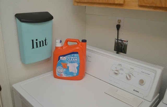 a wall-mounted lint bin in a laundry room