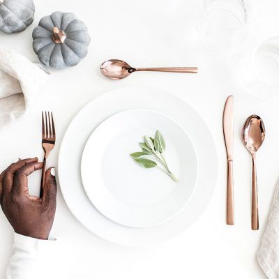 A woman's hand setting a table with copper silverware and decorative pumpkins for Thanksgiving