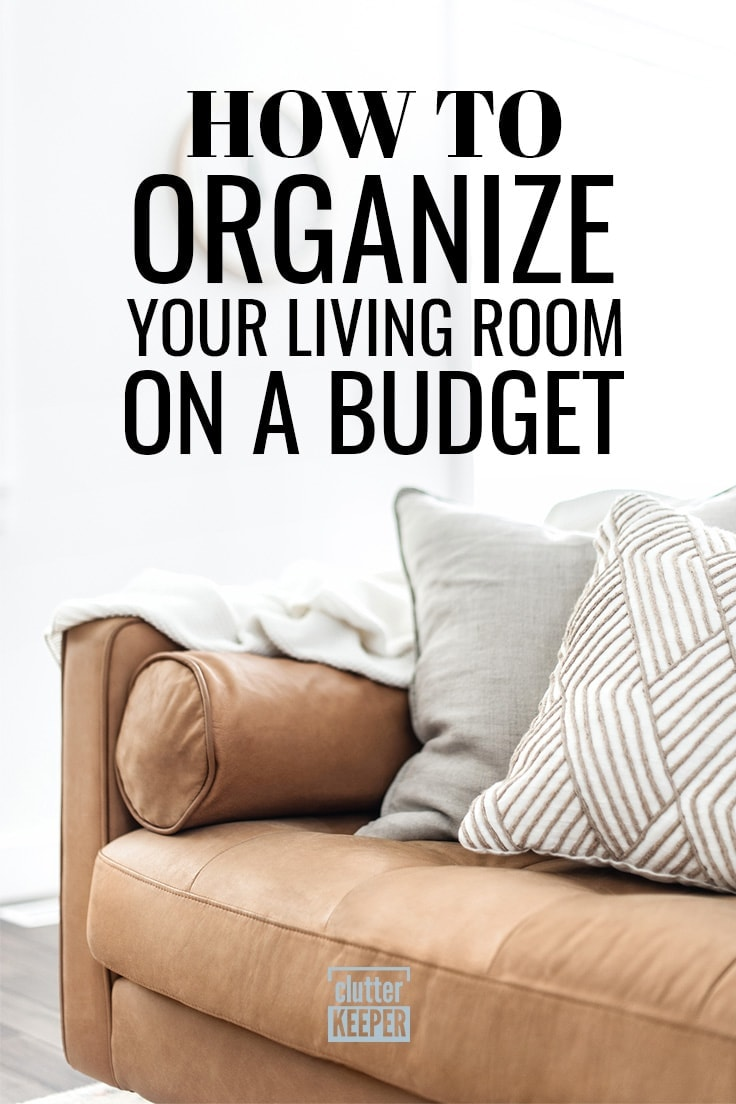 How to Organize Your Living Room on a Budget, a tan leather couch with two pillows and a throw blanket