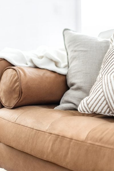 a tan leather couch in a living room with two pillows and a throw blanket