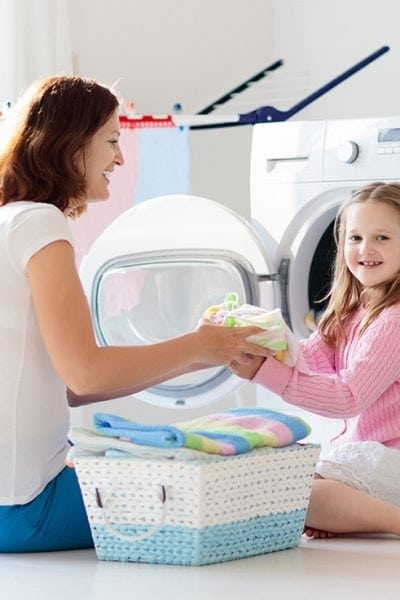 Mother and daughter smiling and folding towels by a washing machine in a laundry room