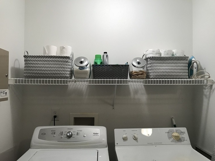 Different sized baskets and jars to store supplies in a laundry room.