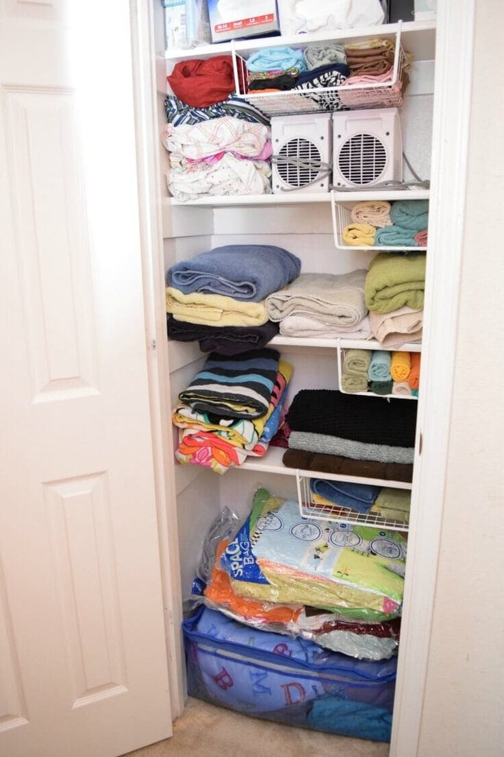 An organized hall closet with sheets, washcloths, and blankets.