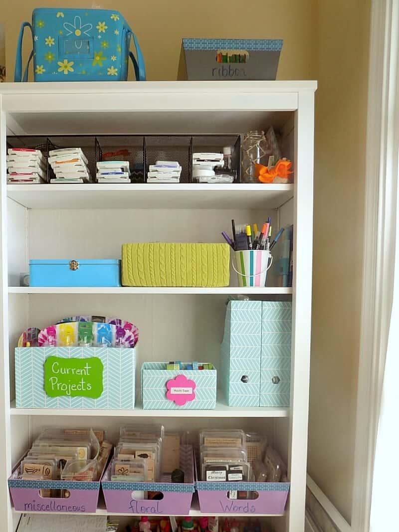 An organized bookshelf filled with art supplies