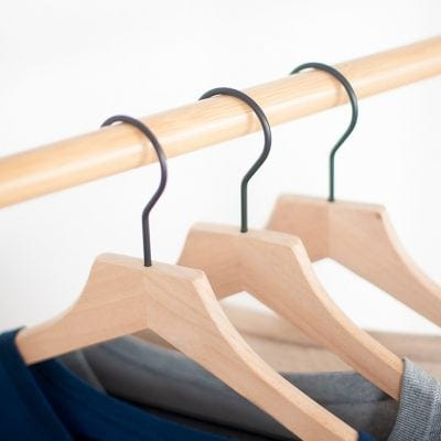 3 wooden hangers on a rod in a closet, using hanging organizers is one of many clever closet ideas