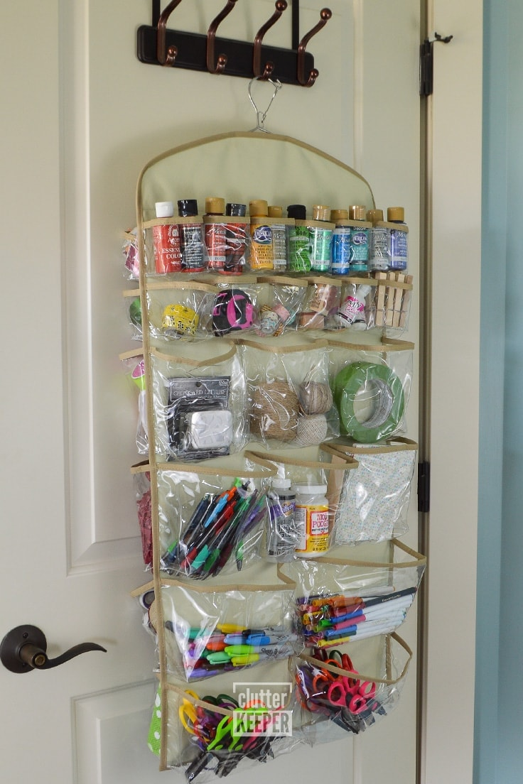 The back side of the 44 pocket hanging organizer from Clutter Keeper® filled with scissors, markers, paint, scrapbook paper and other craft supplies.