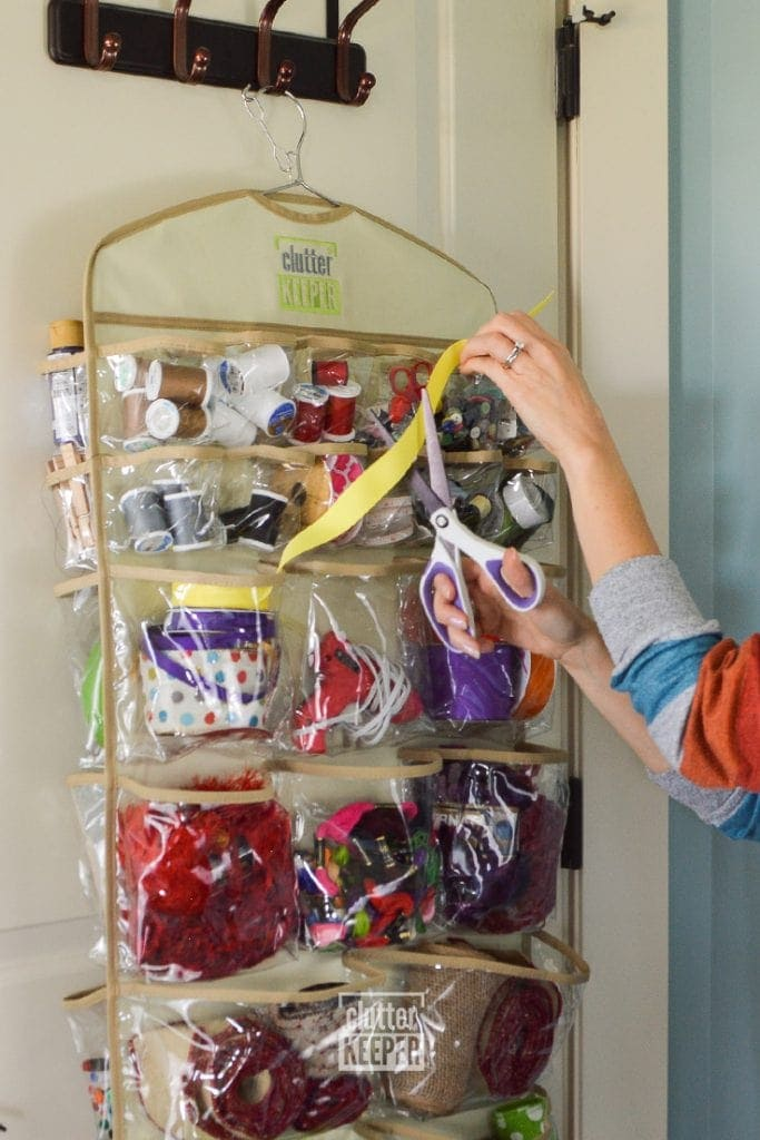 A close up of a woman's hands as she's pulling ribbon out of a hanging organizer and cutting it with scissors