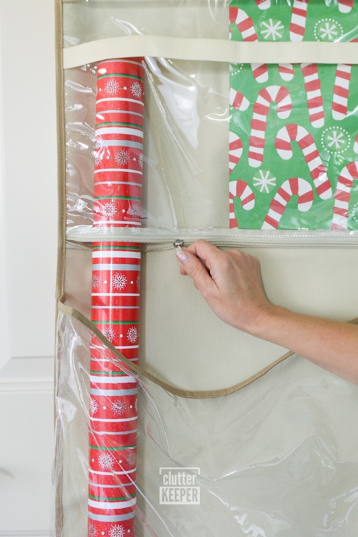 zipping the storage pocket on a hanging gift wrap storage organizer
